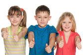 Drie kinderen houden hun duimen omhoog — Stockfoto