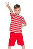 Wesoły chłopiec czerwony pokazuje znak zwycięstwo — Zdjęcie stockowe