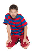Thoughtful young boy in striped shirt on the floor — Stok fotoğraf