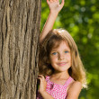 Pretty little girl near a tree — 图库照片