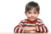 Cute little boy at the desk — Stock Photo