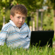 Boy with laptop on the lawn — Stock Photo