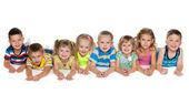 Eight children lying on floor — Stock Photo