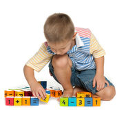 Concentrated little boy with blocks on the floor — Stock Photo
