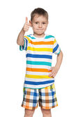 Smiling little boy holds his thumb up — Stock Photo