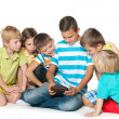 Stock Photo: Group of six children with a new gadget