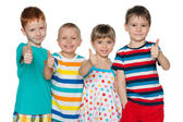 Four cheerful children hold his thumbs up — Stock Photo