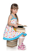 Little girl reading on the pile of books — Stock Photo