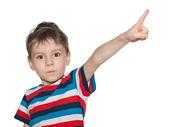 Surprised little boy shows his finger aside — Stockfoto