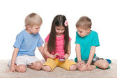 Kids with a gadget on the white carpet — Stock Photo