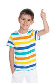 Laughing young boy holds his thumb up — Stockfoto