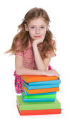 Smiling young girl near books — Stockfoto
