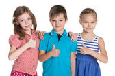 Three cheerful children hold his thumbs up — Stockfoto