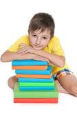 Pensive young boy near books — Stock Photo