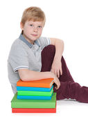 Serious young boy near books — Foto Stock