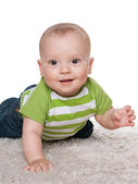 Smiling baby boy on the white carpet — Stock Photo