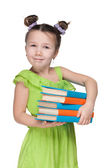 Clever smiling little girl with books — Stockfoto