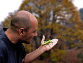 Man holding a green insect — Stock Photo