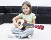 Little girl with guitar sitting on the floor — Stock Photo