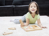 Smile girl playing on the floor — Stock Photo