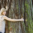 Young woman hugging large tree trunk — Stock Photo