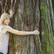 Young woman hugging large tree trunk — Stock Photo #13332606