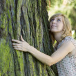 Woman hugging large tree trunk while looking up — Stock Photo