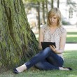 Woman using digital tablet by tree on lawn — Stock Photo