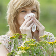 Woman blowing nose into tissue outdoors — Stock Photo