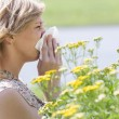 Woman blowing nose into tissue in front of flowers — Stock Photo #13334745