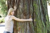 Jonge vrouw knuffelen grote boomstam — Stockfoto