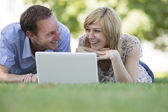 Couple lying on grass with laptop in park — ストック写真