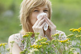 Woman blowing nose into tissue outdoors — Stockfoto