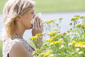 Woman blowing nose into tissue in front of flowers — Stock Photo