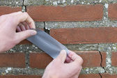 Man Applying Duct Tape On Cracked Wall. — Stock Photo