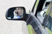 Conducteur visible à travers le miroir de vision latérale de voiture. — Photo