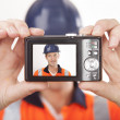 Carpenter taking self portrait with digital camera — Stock Photo #16808559