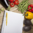 Vegetables with book and pen on wooden surface - Stock Photo