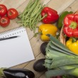 Book with pen and vegetables — Stock Photo