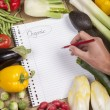 Hand writing list of organic vegetables — Stock Photo