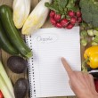 Hand pointing on book with vegetables surface — Stock Photo
