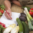 Man's hand writing list of organic vegetables — Stock Photo #16809217