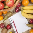 Fruits in basket with pencil and book — Stock Photo