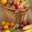 Fruits and basket on wooden surface — Stock Photo