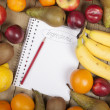 Pencil on book admist fruits — Stock Photo