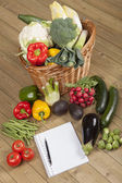 Book with vegetables and basket — Stock Photo