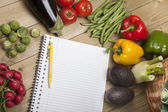 Vegetables with book and pen on wooden surface — Stock Photo