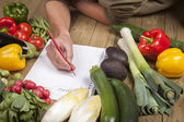 Man's hand writing list of organic vegetables — Stock Photo