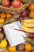 Various fruits in basket with pencil and book — Stok fotoğraf