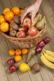 рука, собирание яблоко из корзины — Стоковое фото